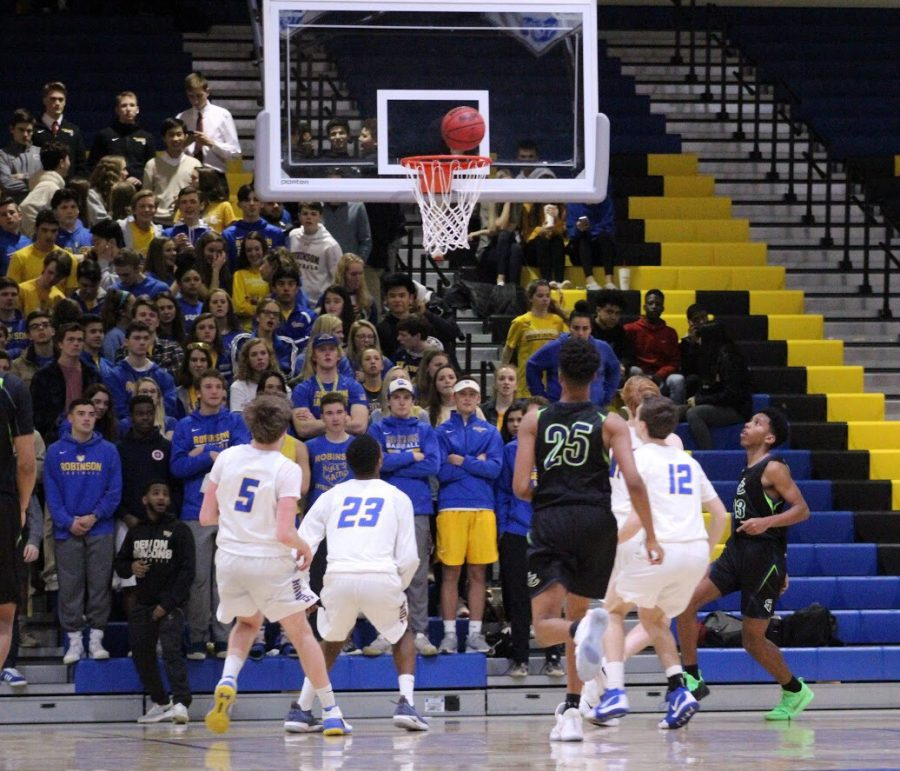The Robinson Hype Squad and players from both teams look as a basketball circulates the basket.