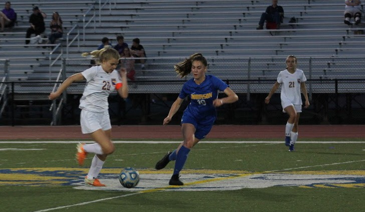 Varsity girls soccer currently has an undeafeated season. Sophomore, Ella Wood runs as she attempts to side swipe the ball from her opponent.