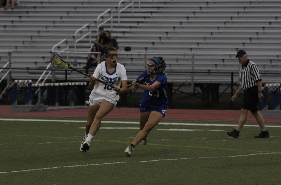 Sophomore, Madeleine Charland runs the ball down the field.