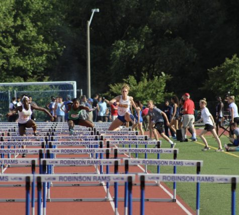 Junior, Olivia Womble goes over a hurdle in the 100 meter event.
