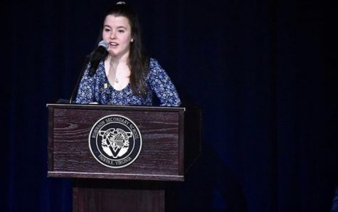Senior Carrie Walker, the National Honors Society president, speaks at the induction ceremony in 2019.